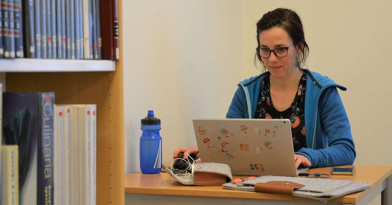 En ung kvinna sitter och arbetar med sin laptop.